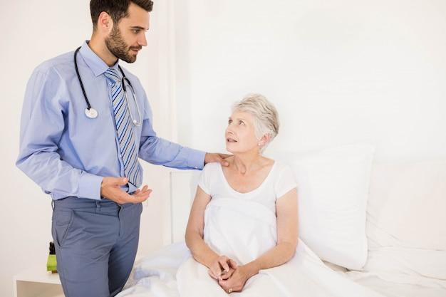 Hübsche hauptkrankenschwester, die mit älterer frau im schlafzimmer spricht