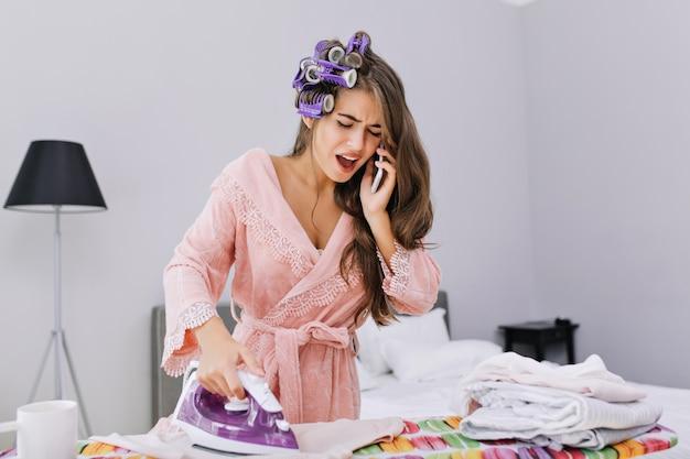 Hübsche hausfrau im rosa bademantel und lockenwickler bügelt kleidung und spricht am telefon. sie sieht erstaunt und beschäftigt aus.