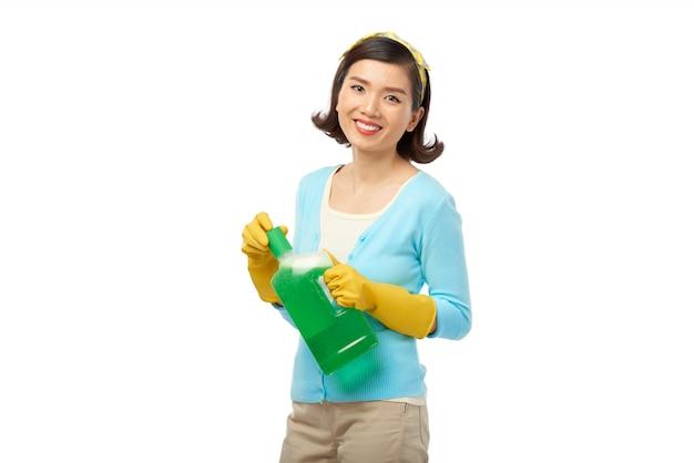 Hübsche hausfrau mit reinigungsmittelflasche