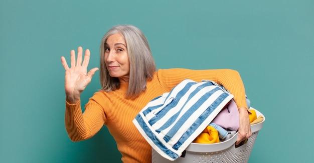 Hübsche haushälterin der grauen haare, die wäsche wäscht