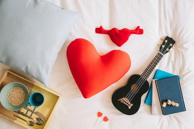 Hübsche herzen und ukulele auf dem bett
