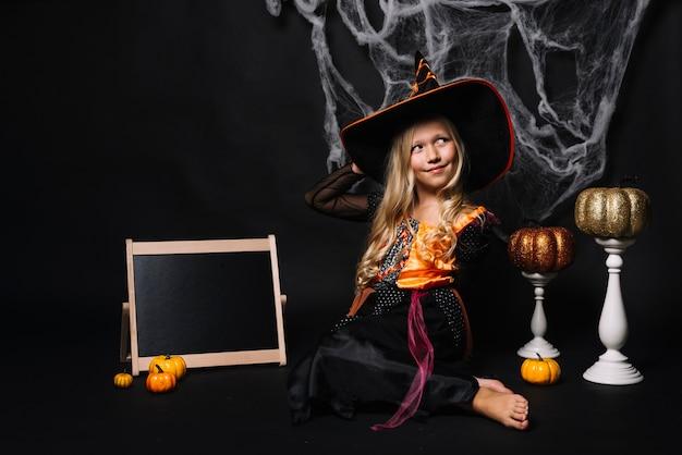 Hübsche hexe mit kürbisen und schild