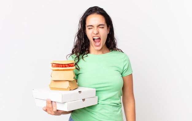 Hübsche hispanische frau, die aggressiv schreit, sehr wütend aussieht und fast-food-boxen zum mitnehmen hält?