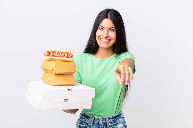 Hübsche hispanische frau, die auf die kamera zeigt, die sie auswählt und fast-food-boxen zum mitnehmen hält?