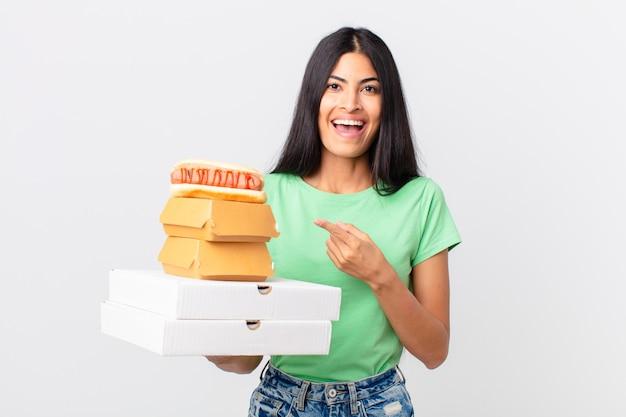 Hübsche hispanische frau, die aufgeregt und überrascht aussieht, auf die seite zeigt und fast-food-boxen zum mitnehmen hält
