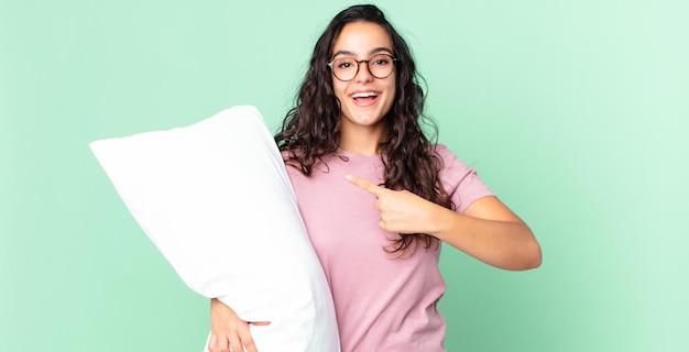 Hübsche hispanische frau, die aufgeregt und überrascht aussieht, auf die seite zeigt und pyjamas mit einem kissen trägt