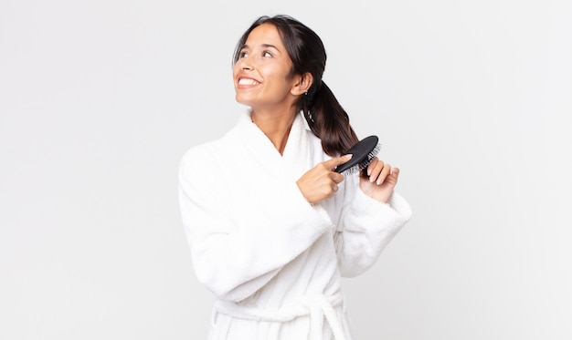 Hübsche hispanische frau, die bademantel trägt und eine haarbürste hält