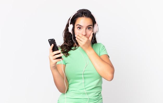Hübsche hispanische frau, die den mund mit den händen mit einem schockierten mit kopfhörern und einem smartphone bedeckt