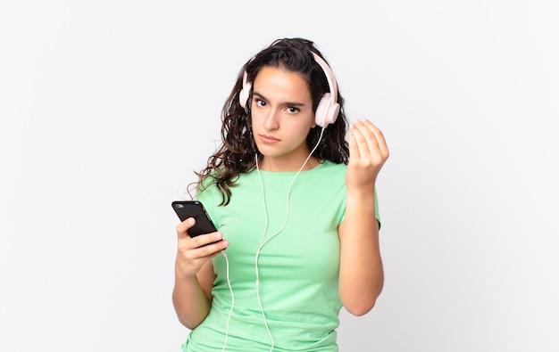 Hübsche hispanische frau, die eine capice- oder geldgeste macht und ihnen sagt, dass sie mit kopfhörern und einem smartphone bezahlen sollen