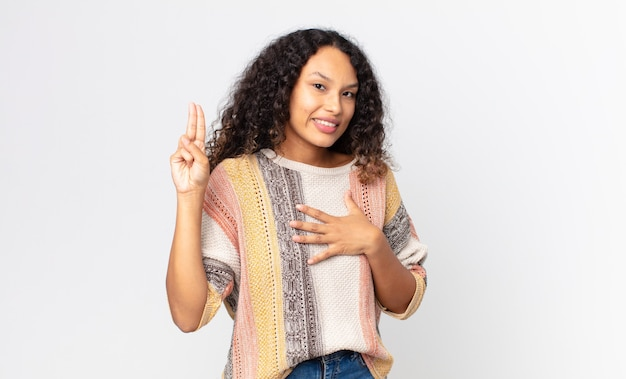 Hübsche hispanische frau, die glücklich, selbstbewusst und vertrauenswürdig aussieht, lächelt und ein siegeszeichen zeigt, mit einer positiven einstellung