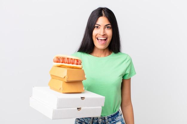 Hübsche hispanische frau, die glücklich und angenehm überrascht aussieht und fast-food-boxen zum mitnehmen hält