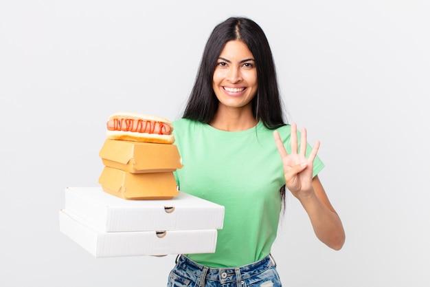 Hübsche hispanische frau, die lächelt und freundlich aussieht, nummer vier zeigt und fast-food-boxen zum mitnehmen hält?
