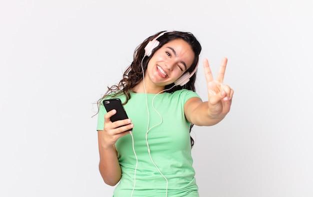 Hübsche hispanische frau, die lächelt und freundlich aussieht und nummer zwei mit kopfhörern und einem smartphone zeigt
