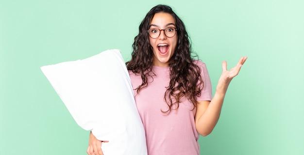 Hübsche hispanische frau, die sich extrem schockiert und überrascht fühlt und einen pyjama mit einem kissen trägt