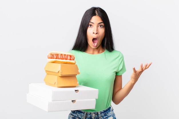 Hübsche hispanische frau, die sich extrem schockiert und überrascht fühlt und fast-food-boxen zum mitnehmen hält