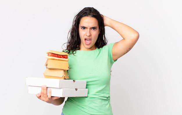 Hübsche hispanische frau, die sich gestresst, ängstlich oder ängstlich fühlt, die hände auf den kopf legt und fast-food-kisten zum mitnehmen hält