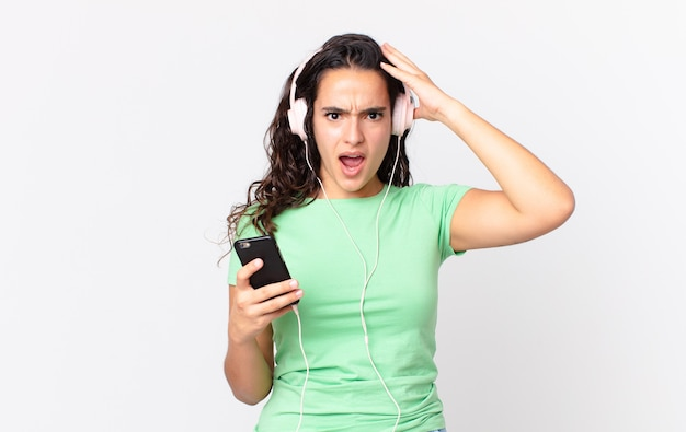 Hübsche hispanische frau, die sich gestresst, ängstlich oder verängstigt fühlt, mit den händen auf dem kopf mit kopfhörern und einem smartphone