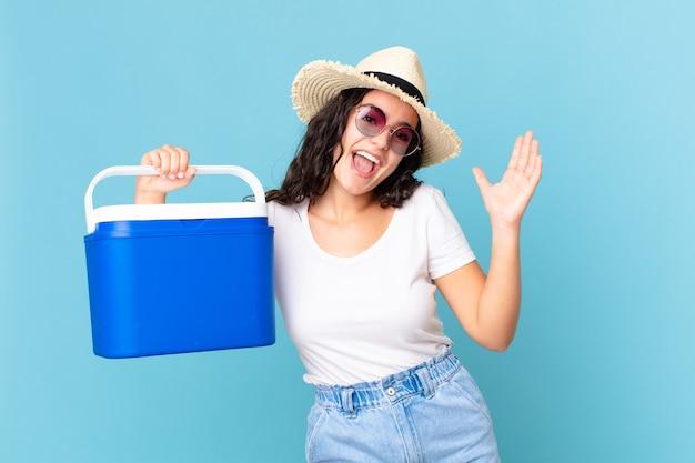 Hübsche hispanische frau, die sich glücklich und erstaunt über etwas unglaubliches fühlt, das einen tragbaren kühlschrank hält