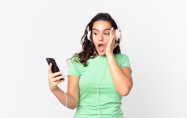 Hübsche hispanische frau, die sich mit kopfhörern und einem smartphone glücklich, aufgeregt und überrascht fühlt