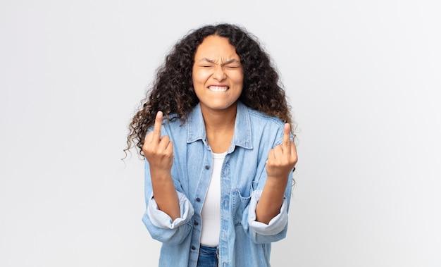Hübsche hispanische frau, die sich provokant, aggressiv und obszön fühlt, den mittelfinger zeigt, mit einer rebellischen haltung