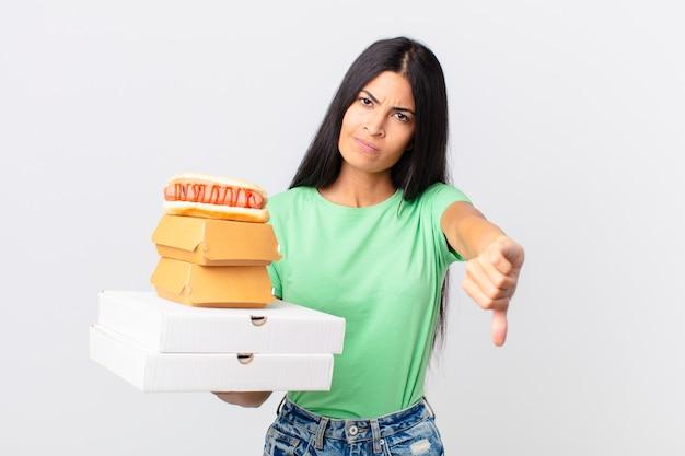 Hübsche hispanische frau, die sich überquert, daumen nach unten zeigt und fast-food-boxen zum mitnehmen hält