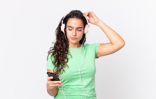Hübsche hispanische frau, die sich verwirrt und verwirrt fühlt und sich mit kopfhörern und einem smartphone am kopf kratzt