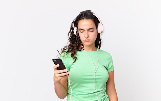 Hübsche hispanische frau, die traurig, verärgert oder wütend ist und mit kopfhörern und einem smartphone zur seite schaut