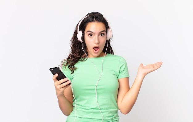Hübsche hispanische frau, die überrascht und schockiert aussieht, mit heruntergefallenem kiefer, die einen gegenstand mit kopfhörern und einem smartphone hält