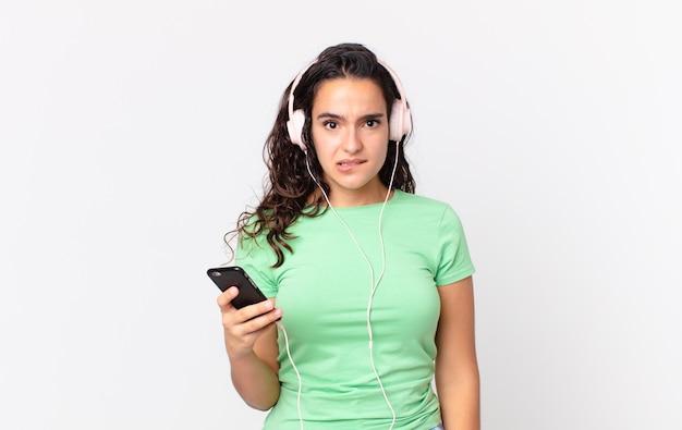 Hübsche hispanische frau, die verwirrt und verwirrt mit kopfhörern und einem smartphone aussieht