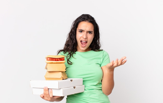 Hübsche hispanische frau, die verzweifelt, frustriert und gestresst aussieht und fast-food-boxen zum mitnehmen hält