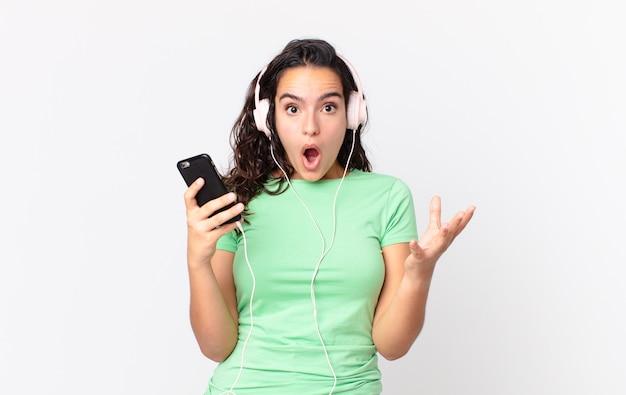 Hübsche hispanische frau erstaunt, schockiert und erstaunt über eine unglaubliche überraschung mit kopfhörer und smartphone