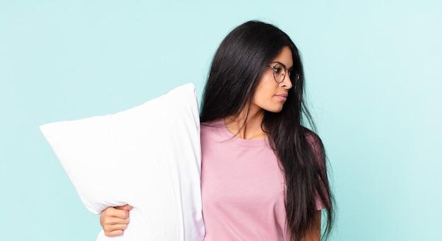 Hübsche hispanische frau in der profilansicht, die nachdenkt, sich vorstellt oder träumt und pyjamas mit einem kissen trägt