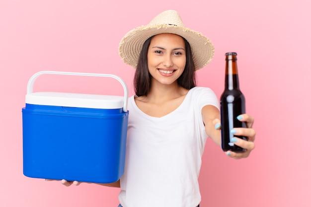 Hübsche hispanische frau mit einem tragbaren gefrierschrank und einem bier