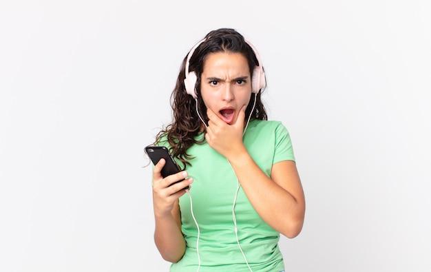Hübsche hispanische frau mit weit geöffnetem mund und augen und hand am kinn mit kopfhörern und einem smartphone