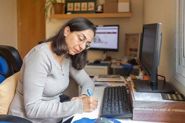 Hübsche hispanische frau mittleren alters, die online-kurs zu hause studiert