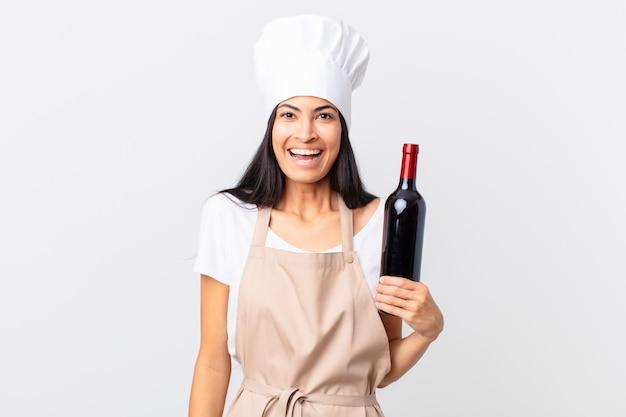 Hübsche hispanische kochfrau, die glücklich und angenehm überrascht aussieht und eine flasche wein hält