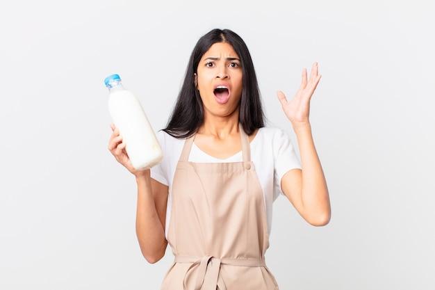 Hübsche hispanische kochfrau, die mit den händen in die luft schreit und eine milchflasche hält