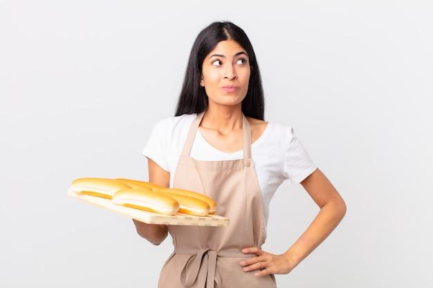 Hübsche hispanische kochfrau, die mit den schultern zuckt, sich verwirrt und unsicher fühlt und ein tablett mit brotbrötchen hält