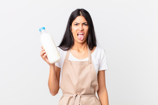 Hübsche hispanische kochfrau, die sich angewidert und irritiert fühlt und die zunge herausstreckt und eine milchflasche hält?