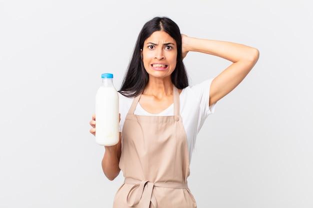 Hübsche hispanische kochfrau, die sich gestresst, ängstlich oder ängstlich fühlt, mit den händen auf dem kopf und einer milchflasche hält