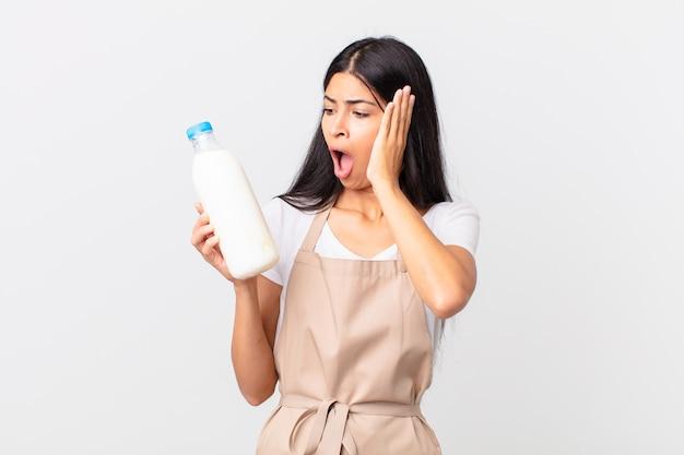 Hübsche hispanische kochfrau, die sich glücklich, aufgeregt und überrascht fühlt und eine milchflasche hält