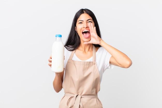 Hübsche hispanische kochfrau, die sich glücklich fühlt, mit den händen neben dem mund einen großen schrei ausspricht und eine milchflasche hält