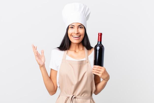 Hübsche hispanische kochfrau, die sich glücklich fühlt, überrascht, eine lösung oder idee zu realisieren und eine flasche wein zu halten?