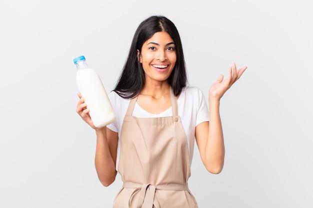 Hübsche hispanische kochfrau, die sich glücklich fühlt, überrascht, eine lösung oder idee zu realisieren und eine milchflasche zu halten