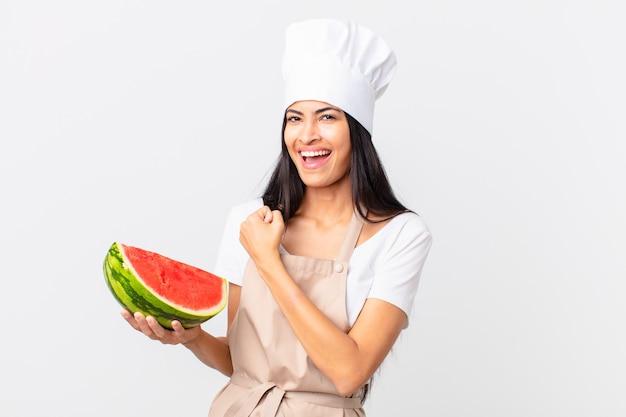 Hübsche hispanische kochfrau, die sich glücklich fühlt und einer herausforderung gegenübersteht oder eine wassermelone feiert und hält