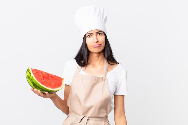 Hübsche hispanische kochfrau, die sich traurig und weinerlich mit einem unglücklichen blick fühlt und weint und eine wassermelone hält