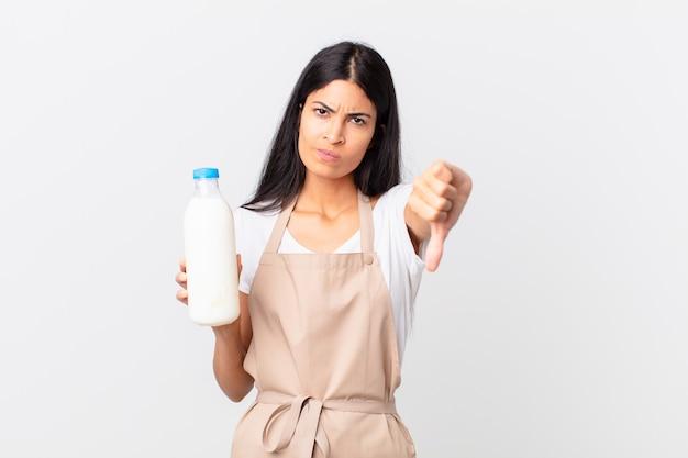 Hübsche hispanische kochfrau, die sich überquert, daumen nach unten zeigt und eine milchflasche hält