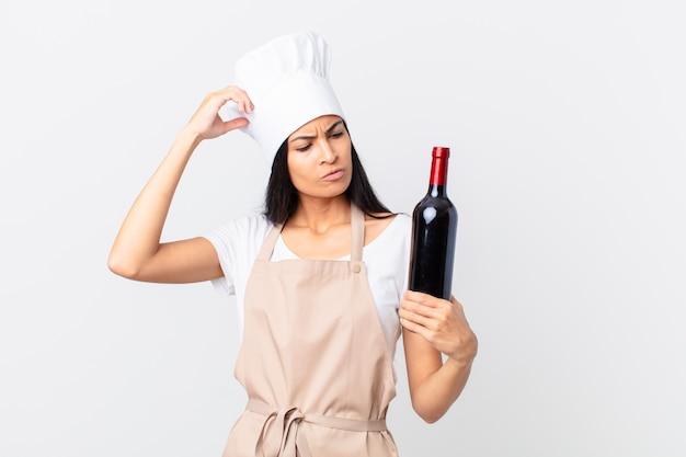 Hübsche hispanische kochfrau, die sich verwirrt und verwirrt fühlt, den kopf kratzt und eine flasche wein hält