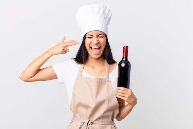 Hübsche hispanische kochfrau, die unglücklich und gestresst aussieht, selbstmordgeste, die ein waffenzeichen macht und eine flasche wein hält