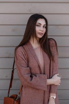 Hübsche hübsche junge frau mit schönem haar in langem jugendfrühlingsmantel mit modischer lederhandtasche steht in der nähe der hölzernen weinlesewand in der stadt europäisches mädchen mit schönem lächeln, das in der straße aufwirft.
